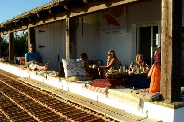 People chilling on the balcony of the main house of A Frame Surfcamp